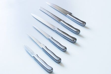 Set of steel kitchen knives, isolated on table photo