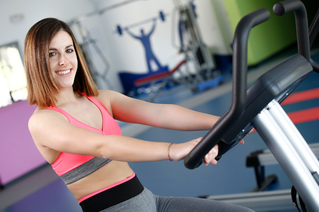 uses: Young woman uses stationary bicycle trainer on gym