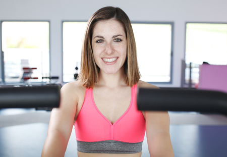 Young woman uses stationary bicycle trainer on gym photo