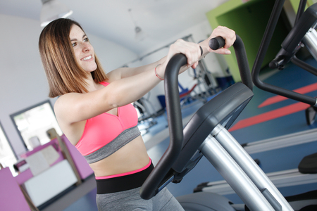stationary bicycle: Young woman uses stationary bicycle trainer on gym