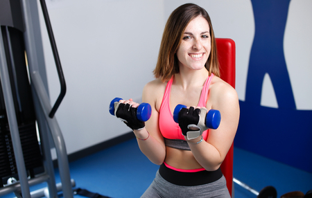 Strong woman weightlifting at the gym looking happy. photo