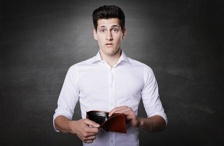 billfold: Attractive brunette young business man holding out empty billfold. Stock Photo