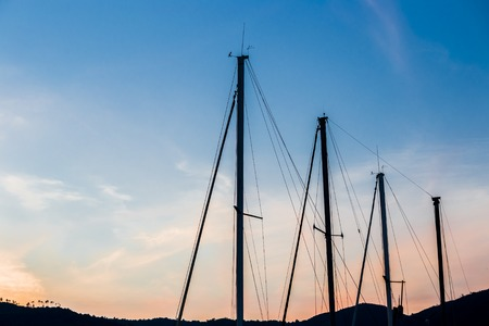 bowsprit: Silhouette of an one-masted touring boat in a harbor at sunset.