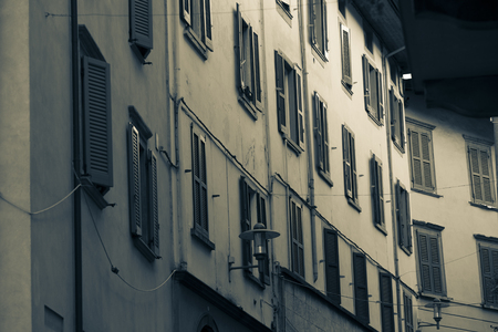 saluzzo: Facade of typical italian house with colorful windows and doors in town of lovere north italy.