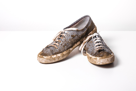 muddy clothes: very Muddy Trainers  white shoes on white background. Stock Photo