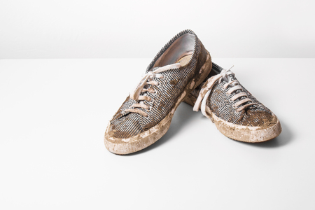 very Muddy Trainers  white shoes on white background. Stock Photo