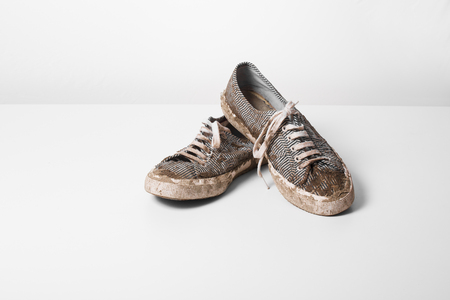 very Muddy Trainers  white shoes on white background. Archivio Fotografico