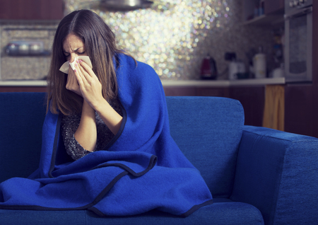 Sick young woman is coughing and blowing. Stock Photo