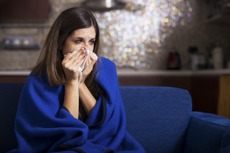sick person: Sick young woman is coughing and blowing. Stock Photo