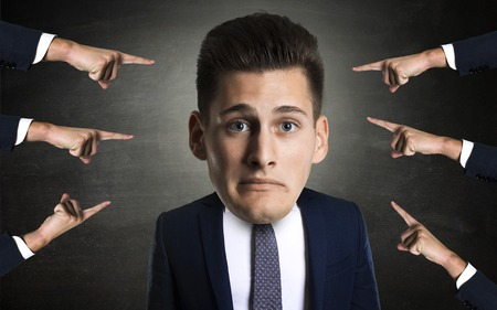 mobbing: concept of mobbing with portrait of a young employee with many arms pinting at him. Stock Photo