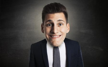 unprofessional: Funny businessman portrait with big head on blackboard backgorund