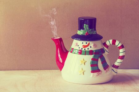 coming: beautiful christmas style  kettle on grunge  wooden background with smoke coming out of it Stock Photo