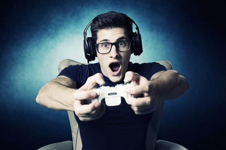 zábava: videohry závislý mladý kluk hraje s konzolou.