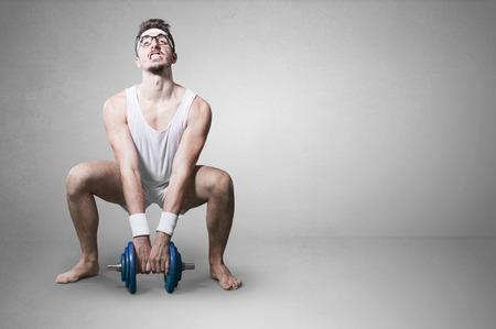 levantar pesas: joven empollón tratar de levantar pesas.