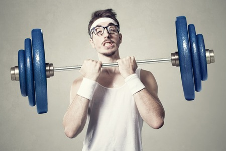 nerd: young nerd try to lift weights. Stock Photo