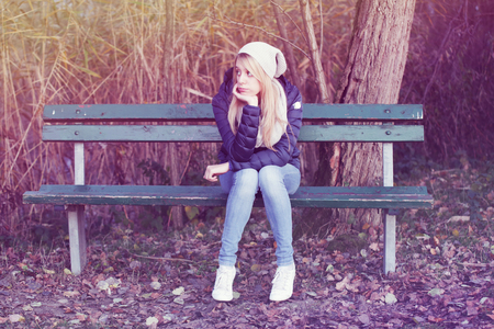 late 20s: young blonde  bored girl on a bench.