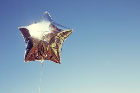 pallone d'argento stella sul cielo con filtri di colore Archivio Fotografico
