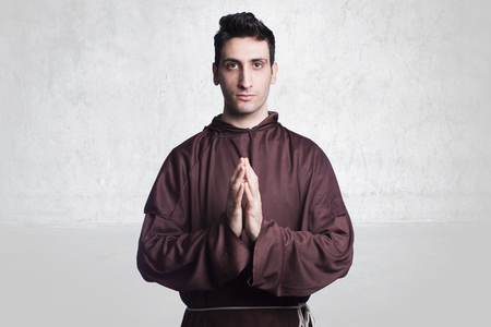 friar: young friar with habit praying on background.