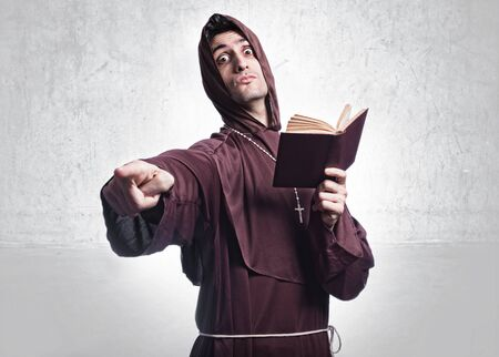 friar: young priest pointing at camera angry and with bible in the other hand