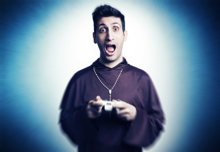 friar: young friar playing with console joystick on grunge background Stock Photo