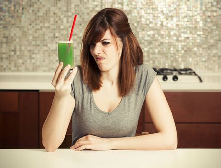 young woman dont want drink disgusting green diet drink . Stock Photo