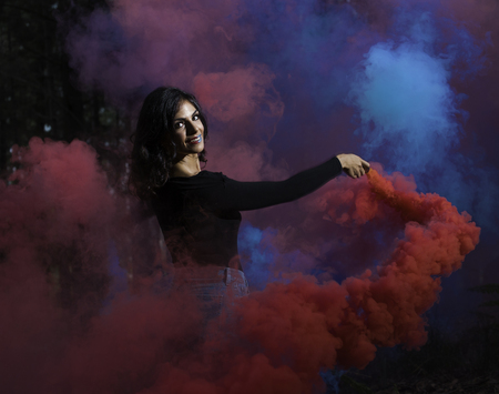 young girl dancing with colored smoke in the woods Archivio Fotografico