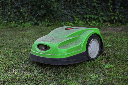 broken robotic lawnmower with a lot of dust in home garden Фото со стока