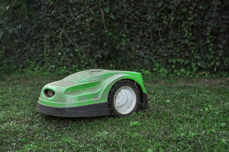 broken robotic lawnmower with a lot of dust in home garden Stock Photo