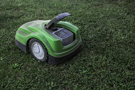 broken robotic lawnmower with abroken robotic lawnmower with a lot of dust in home garden. lot of dust in home garden Фото со стока
