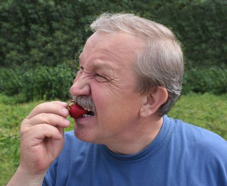 Elderly man, eating a red strawberry  Stock Photo - 3223120