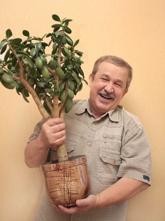 Cheerful elderly the man with a flowerpot Stock Photo - 3632999
