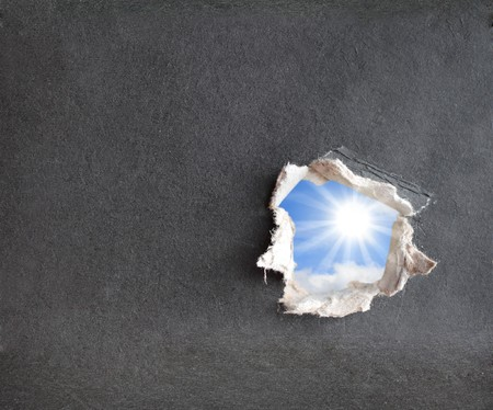 Hole with the fragmentary edges, punched in a cardboard photo