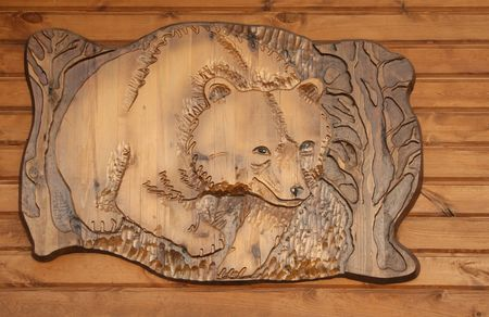 Decorative carved panel with a brown bear photo