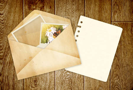 Old envelope with photos on wooden planks photo