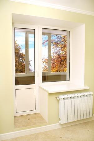 balcony door: Empty room, closed window. Vertical photo