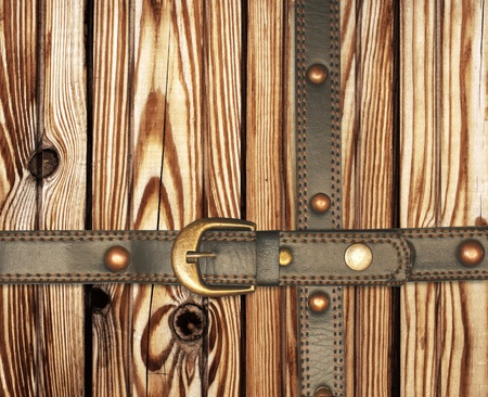 Grunge background. Old wooden boards and leather belt photo