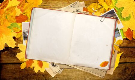 Old book, autumn leaves and photos. Objects over wooden planks photo