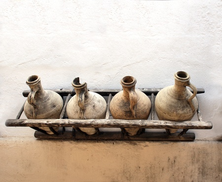 Ancient pitchers on stucco wall photo