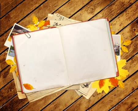 Old book, autumn leaves and photos. Objects over wooden planks