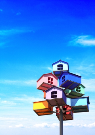 domiciles: Colorful nesting boxes on blue sky