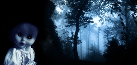 Vintage evil spooky doll and mysterious landscape of foggy forest photo