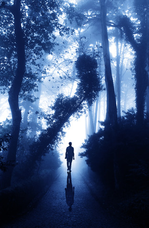 lonely road: Man on road in foggy forest Stock Photo