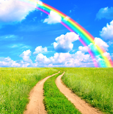 Rural summer landscape with old road and rainbow