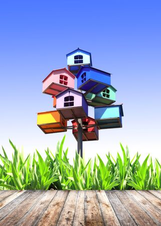 Summer grass, old wooden planks and nesting boxes on blue background photo