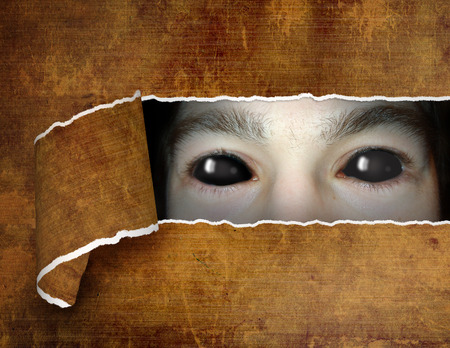 Dark series - a look from darkness. Monster eye in hole in the paper photo
