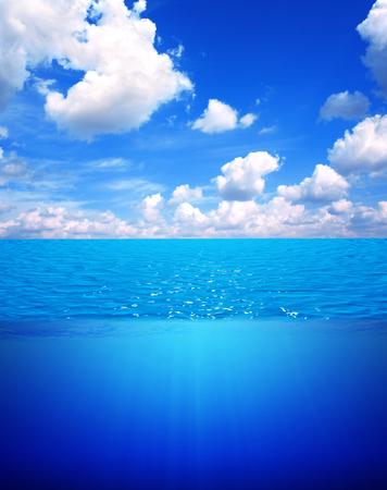 vertical: Escena subacuática y el cielo azul con nubes blancas. La superficie del agua dividida por la línea de flotación