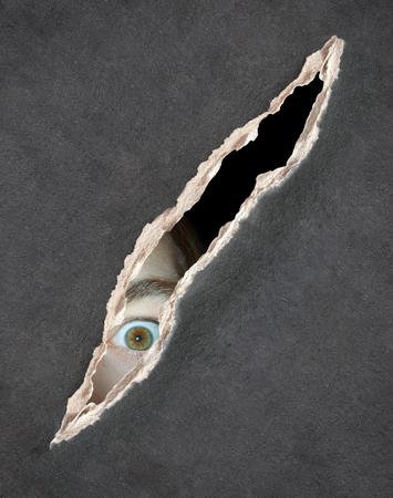 eye hole: Dark series - a look from darkness. Eyes of young man looking into a hole in a paper