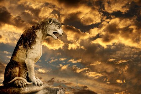 ancient lion: Beautiful sunset, ancient lion statue and storm sky