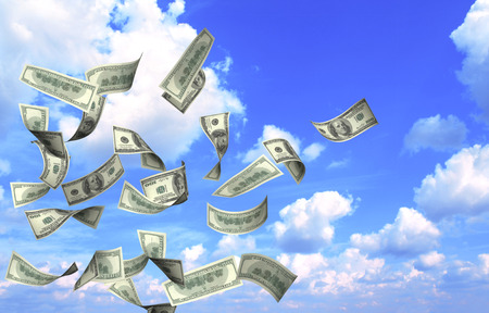 dollar: Flying banknotes of dollars on blue sky background Stock Photo
