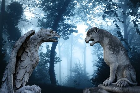 gargoyle: Ancient eagle statue and lion statues in mysterious landscape of foggy forest